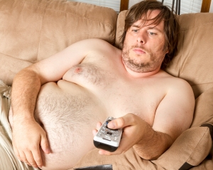 Fat man is laying on the couch topless watching the TV. Guy is overweight and quite lazy looking.
